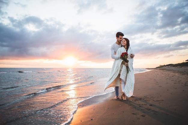 Casal andando na praia com um buquê de rosas ao pôr do sol Foto gratuita