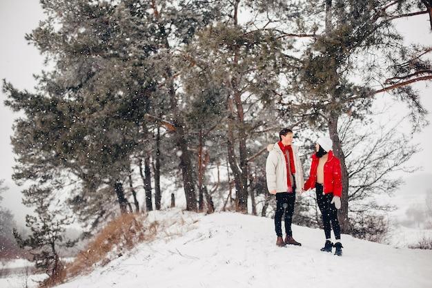 Casal apaixonado andando em um parque de inverno Foto gratuita