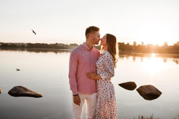 Casal apaixonado beijando no lago ao pôr do sol. lindo casal jovem apaixonado andando na margem do lago ao pôr do sol nos raios de luz brilhante. copie o espaço Foto Premium