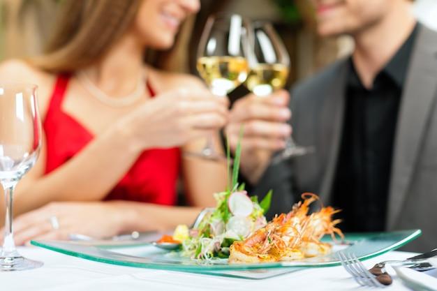 Casal apaixonado, brindando com champanhe no restaurante Foto Premium