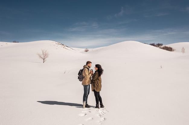 Casal apaixonado caminha no inverno na neve. homem e mulher viajando. casal apaixonado nas montanhas. Foto Premium