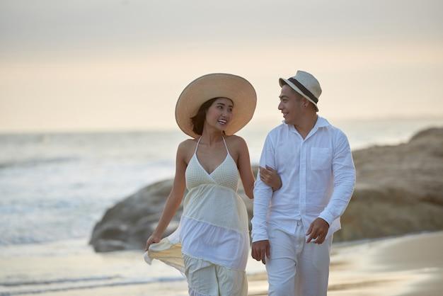 Casal apaixonado caminhando à beira-mar Foto gratuita