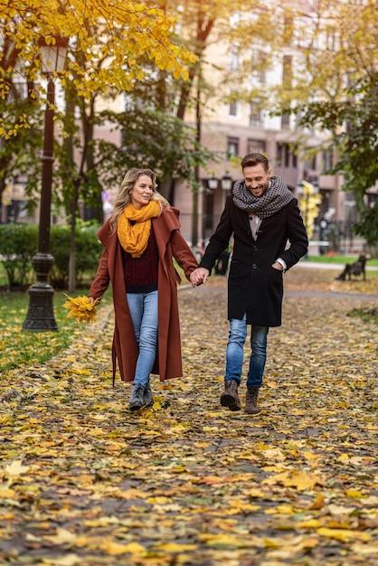 Casal apaixonado, caminhando no parque outono de mãos dadas. foto ao ar livre de um jovem casal apaixonado Foto Premium