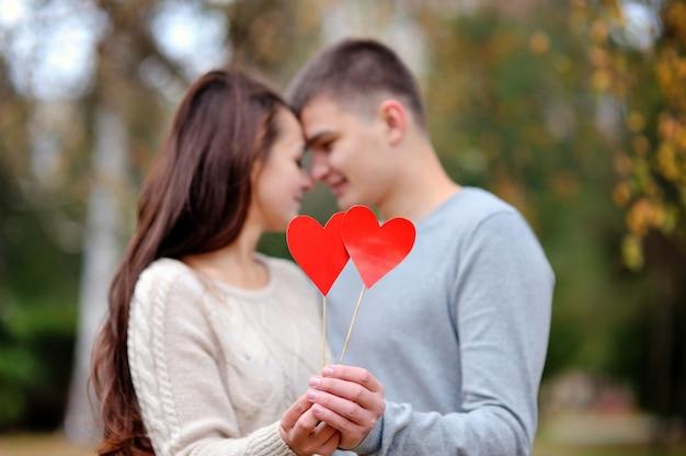 Casal apaixonado com coração vermelho no parque outono. dia dos namorados namoro conceito de amor Foto Premium
