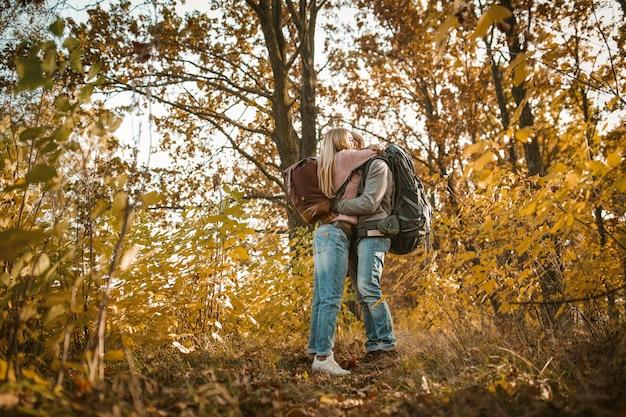 Casal apaixonado de abraços de viajantes admirando a natureza do outono. os jovens estão abraçando entre a natureza multicolorido do outono. disparado por baixo. conceito de amor e caminhadas Foto Premium