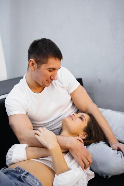 Casal apaixonado, deitado em uma cama branca. homem mulher, abraçando Foto Premium
