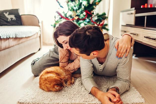Casal apaixonado, deitado pela árvore de natal e brincando com o gato em casa. homem mulher, relaxante Foto Premium