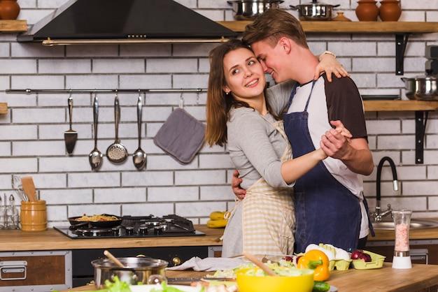 Casal apaixonado em aventais dançando na cozinha Foto gratuita