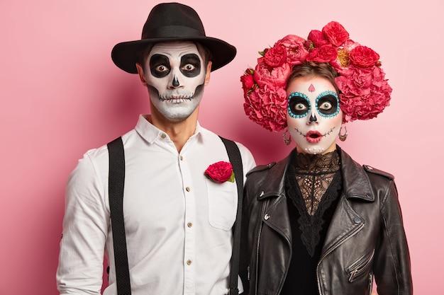 Casal apaixonado em fantasias de esqueletos e maquiagem de crânio, tem expressões de medo, comemora o feriado de outono, posa durante a festa de terror, isolado sobre o fundo rosa. conceito de feliz dia das bruxas Foto gratuita