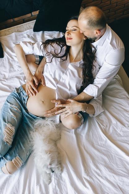 Casal apaixonado grávido deitar na cama afago, à espera de bebé Foto Premium