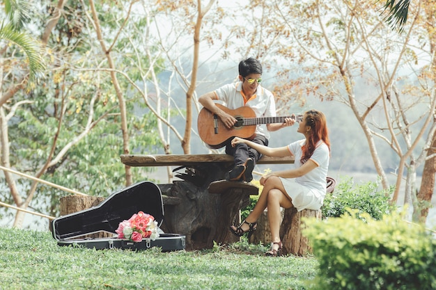 Casal apaixonado por tocar violão na natureza Foto gratuita