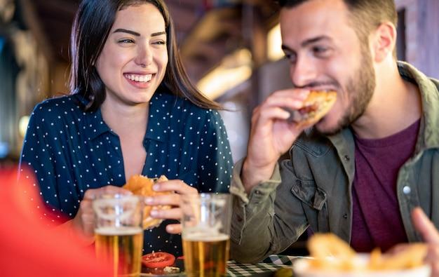 Casal apaixonado se divertindo comendo hambúrguer no bar do restaurante Foto Premium