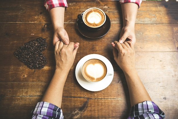 Casal apaixonado, segurando o café da mão na mesa de madeira ...