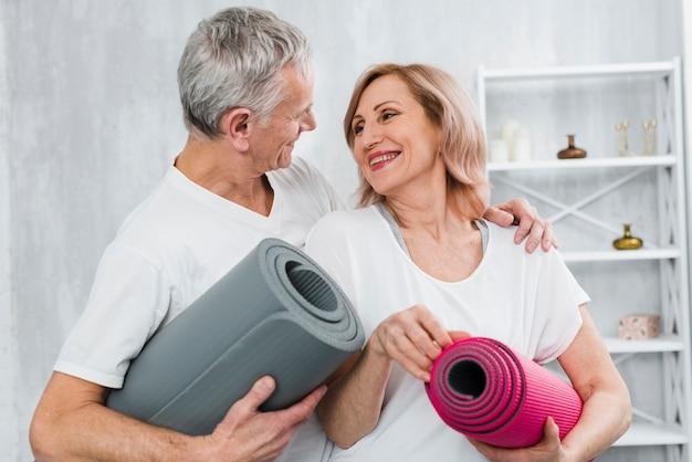 Casal apaixonado, segurando o tapete de ioga, olhando um ao outro Foto gratuita