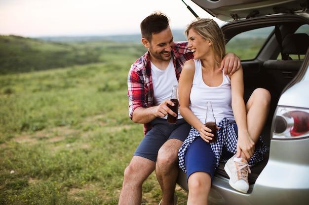 Casal apaixonado, sentado no depósito de carros durante a viagem na natureza Foto Premium