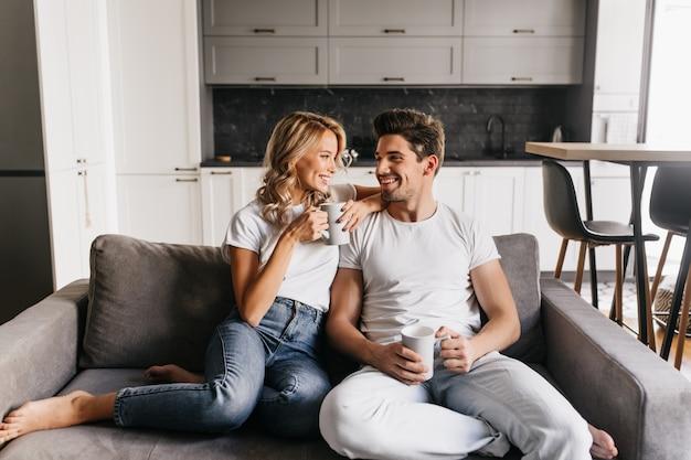 Casal apaixonado, sentado no sofá, segurando copos, olhando um para o outro e sorrindo. casal romântico gosta de manhã juntos em casa. Foto gratuita