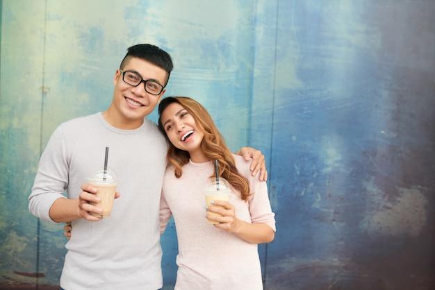 Casal apaixonado sorrindo alegremente segurando milkshakes Foto gratuita