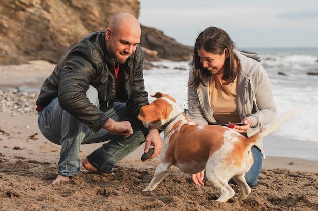 Casal aproveitando o tempo com cachorro Foto gratuita