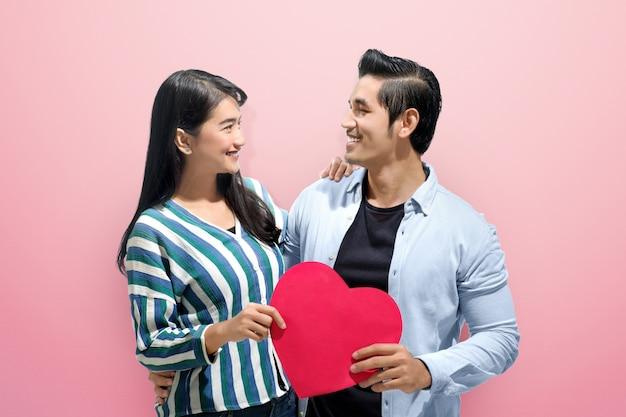 Casal asiático alegre abraçar e segurando corações de papel vermelho Foto Premium