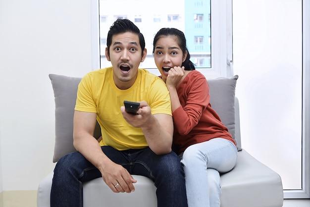 Casal asiático animado sentado no sofá e assistir a filmes Foto Premium