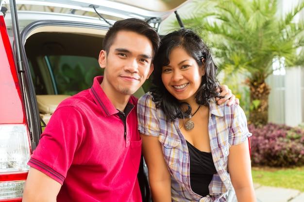 Casal asiático é feliz na frente do carro Foto Premium
