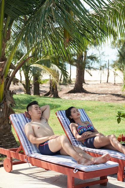 Casal asiático relaxante nas espreguiçadeiras no resort tropical Foto gratuita