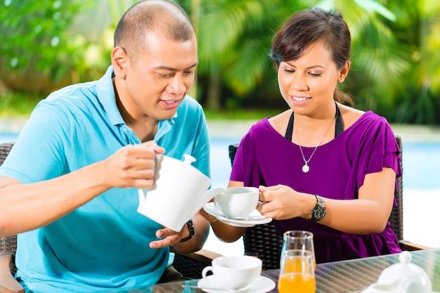 Casal asiático tomando café na varanda de casa Foto Premium