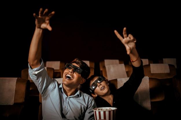 Casal assiste filme no cinema com sorriso de pipoca e sorriso no rosto Foto Premium