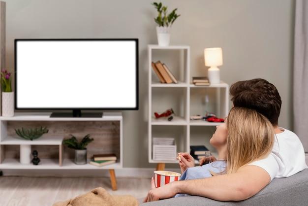 Casal assistindo tv e comendo pipoca Foto gratuita