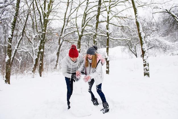 Casal ativo de adolescentes fazendo boneco de neve Foto Premium