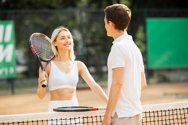 Casal ativo na quadra de tênis Foto gratuita