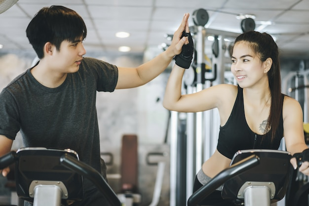 Casal atraente andando na bicicleta girando e dando um ao outro mais cinco no ginásio. trabalhando juntos Foto Premium