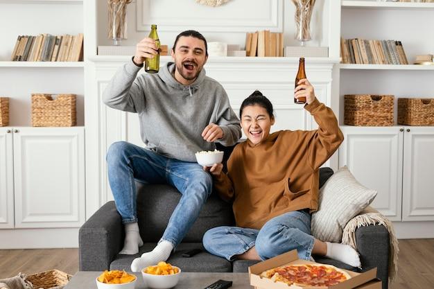 Casal bebendo cerveja e comendo lanches dentro de casa Foto gratuita