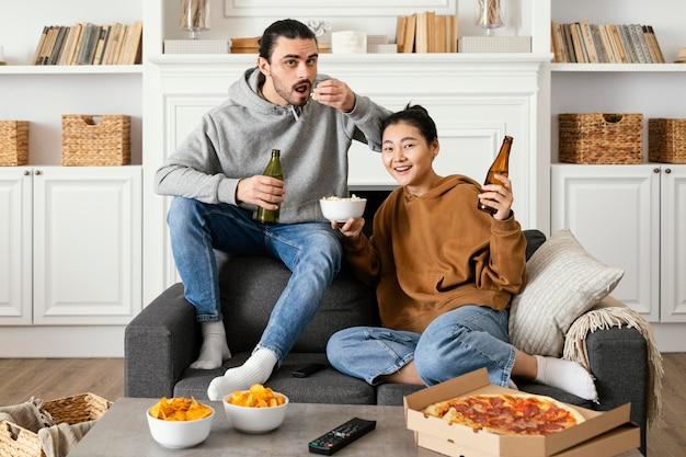 Casal bebendo cerveja e comendo salgadinhos Foto gratuita