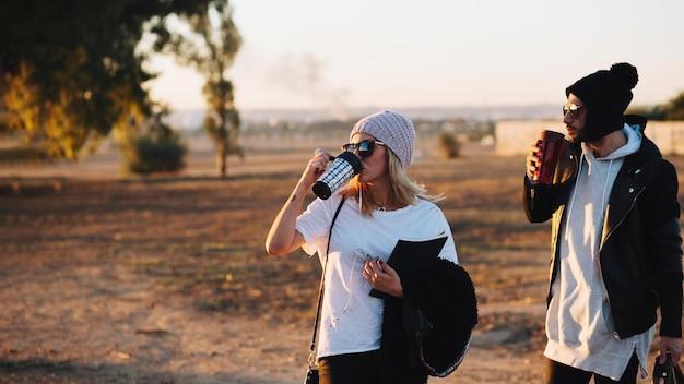 Casal bebendo durante a caminhada no campo Foto gratuita