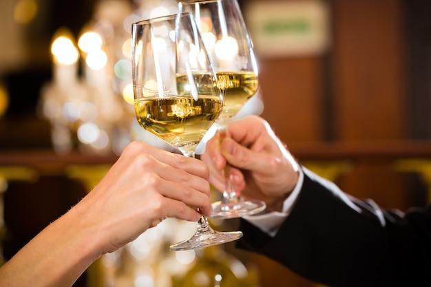 Casal bebendo vinho e copos tilintando, closeup Foto Premium