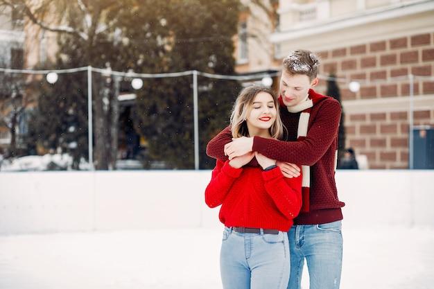 Casal bonito e amoroso um suéteres vermelhos em uma cidade de inverno Foto gratuita