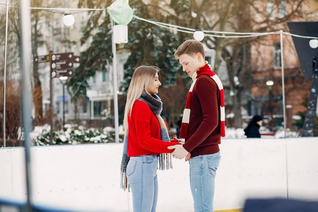 Casal bonito em um suéter vermelho se divertindo em uma arena de gelo Foto gratuita