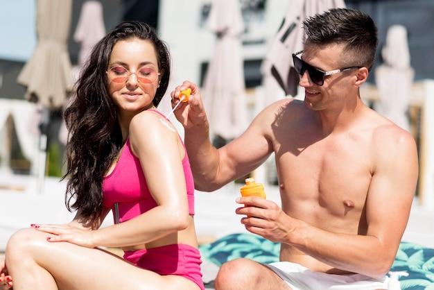 Casal bonito na praia com protetor solar Foto gratuita