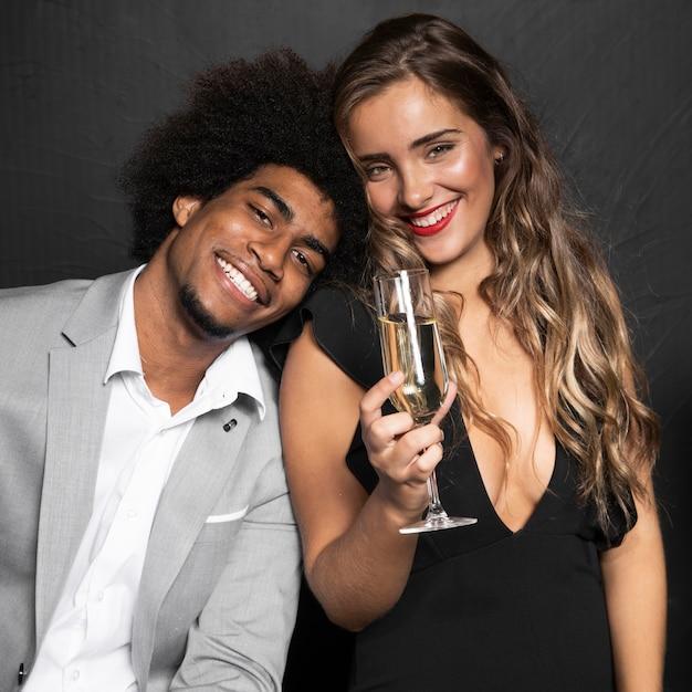 Casal bonito sorridente segurando uma taça de champanhe Foto gratuita