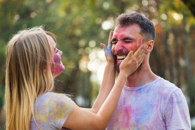Casal brincando com tinta em pó Foto gratuita