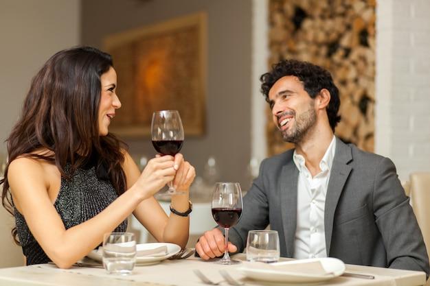 Casal brindando o copo de vinho em um restaurante de luxo Foto Premium