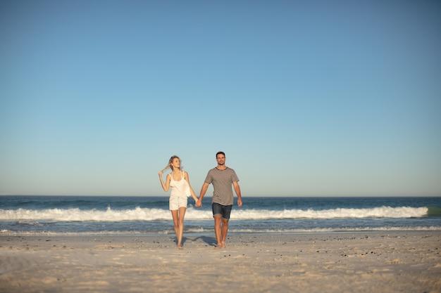 Casal caminhando juntos de mãos dadas na praia Foto gratuita