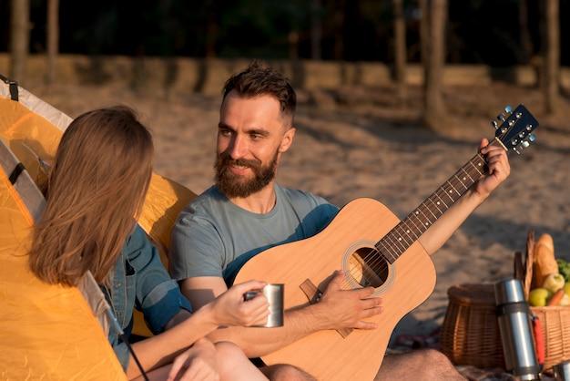 Casal cantando e olhando um para o outro pela tenda Foto gratuita