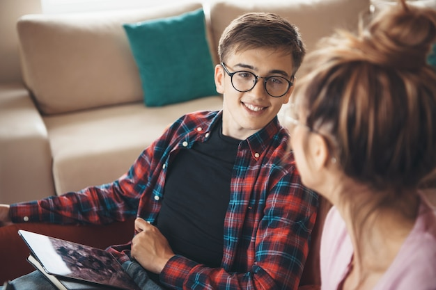 Casal caucasiano encantador com óculos discutindo e sorrindo enquanto usa um tablet Foto Premium