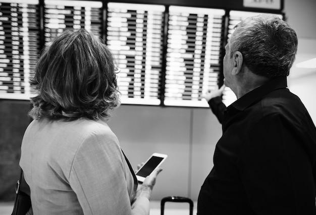 Casal caucasiano está verificando o horário de voo Foto gratuita