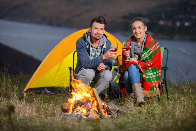 Casal charmoso perto de um fogo enquanto acampar bebendo vinho Foto Premium