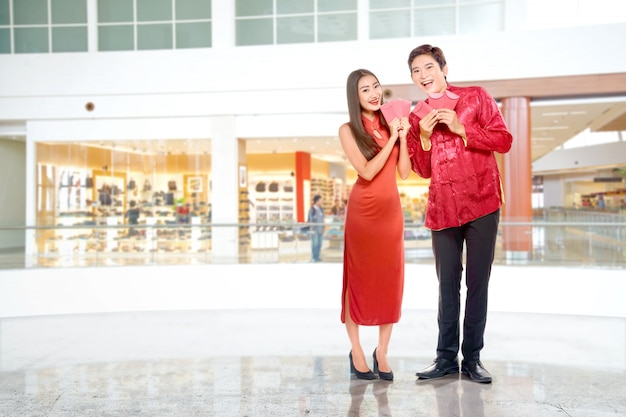 Casal chinês asiático no vestido cheongsam segurando envelopes vermelhos Foto Premium