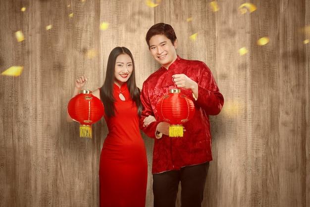 Casal chinês asiático no vestido cheongsam segurando lanterna chinesa Foto Premium