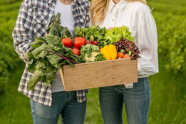 Casal close-up com cesta de legumes Foto gratuita